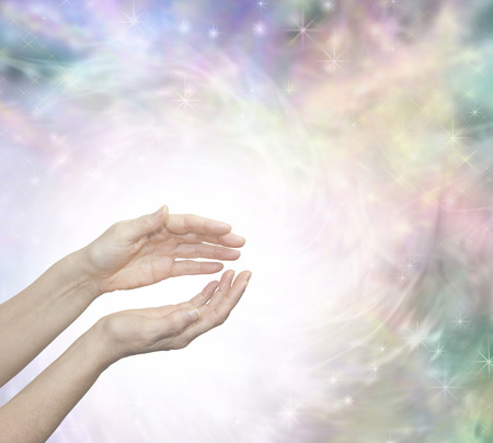 channeling: Faith Healing with Blissful Energy - Outstretched female healing hands surrounded by a large radiating circle of white light and a subtle pastel colored ethereal energy field in background Stock Photo