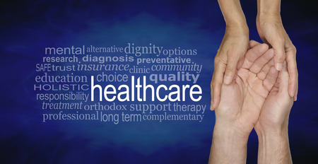 long term care services: Health Care Word Cloud - female hands gently cradling male hands on a misty blue vignette background with a healthcare word cloud to the left