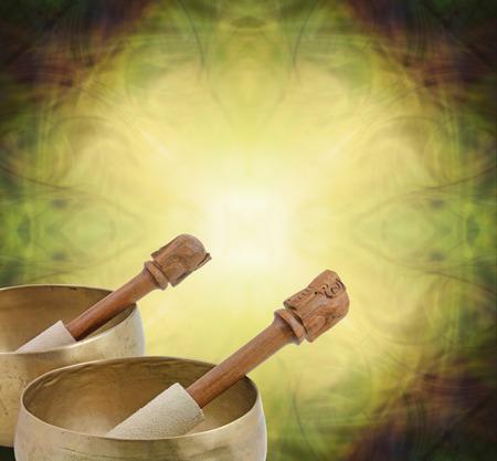 Tibetaanse zingende kommen - twee kommen bijgesneden in de linkerbenedenhoek met ruimte voor een kopie rondom op een ronde mosterdgele oosterse thema patroon achtergrond