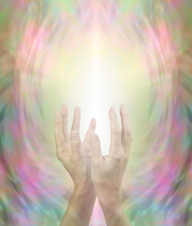 healing chi spiritual: Beaming Beautiful Healing Energy - female hands held in gently cupped upright position with a stream of light streaming up on a golden pink and green background