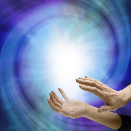 extrasensory: Sensing Supernatural Vortex Field - female hands on the edge of a large blue vortex energy field with central white light and copy space  above