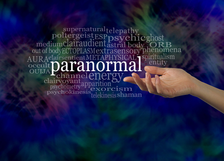 telepathy: Aspect of the Paranormal Word Cloud - female hand gesturing towards the word PARANORMAL surrounded by a relevant word cloud on a dark energy formation background with copy space below Stock Photo