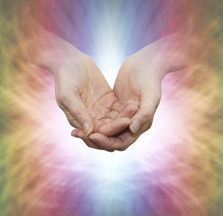 prana: Faith Healer with Divine Light - female hands in gentle cupped position on a multicolored background with a shaft of white light and butterfly shaped pattern