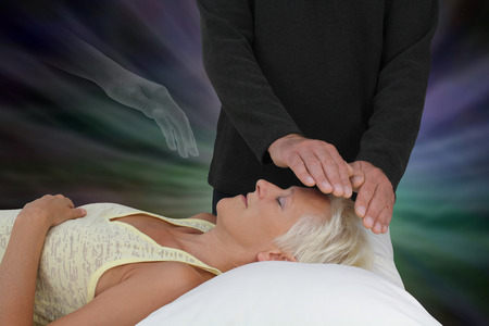 Spirit Assisting Healing Session -  male healer channeling healing energy to supine resting female with the transparent hand of a spirit healing guide floating above heart chakra photo