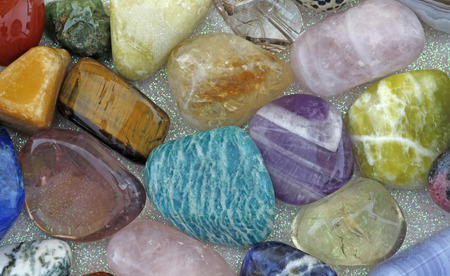 sodalite: Close up of Healing Crystals - Various tumbled stones on an iridescent background including amazonite, ametrine, citrine, rose quartz, emerald, smokey quartz, jasper and tigers eye