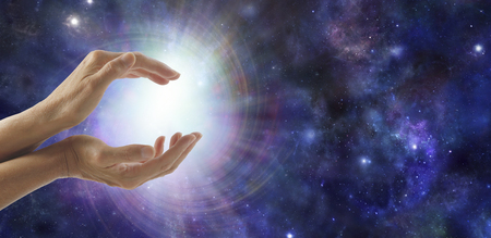 universal healer: Life Force Energy - side view of female cupped hands with a bright vortexing burst of light on a dark blue deep space background with copy space to the right