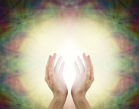 prana: Prana Healing Energy Field - Female energy worker with hands outstretched and open upwards sensing white healing energy on pale yellow background with dark vignette edges