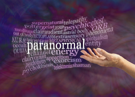 clairvoyant: Paranormal Phenomena Word Cloud - female hand gesturing towards the word PARANORMAL surrounded by a moving word cloud on a dark energy formation background with copy space
