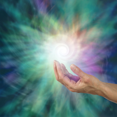 outwards: The Infinite Spiral of Life - open palm with a bright white spiraling light form floating above  expanding outwards on a green and purple ethereal energy background Stock Photo