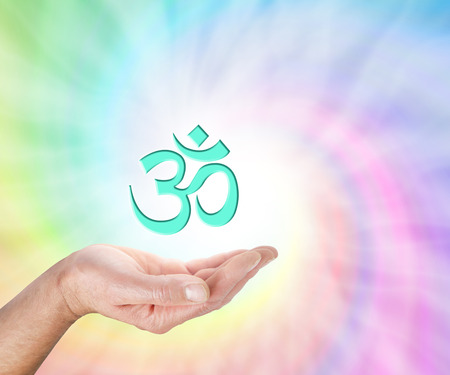 ancient yoga: Offering Om Symbol - male hand with palm facing up and a light green OM symbol floating above on a rainbow colored spiral background and copy space Stock Photo