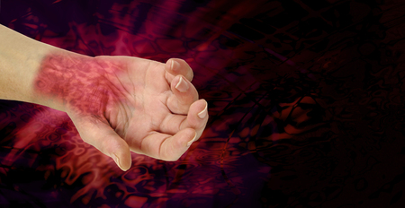 ergonomics: The PAIN of RSI - wrist and hand palm face up showing painful looking nasty redness across wrist area symbolizing the pain of RSI on a black and angry red wide background representing pain