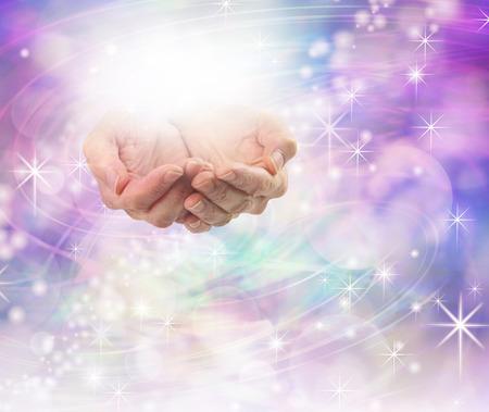 Luz divina energía curativa - Mujeres manos ahuecadas con una bola de energía brillante por encima en un fondo hermoso campo espumoso de color rosa púrpura de energía bokeh con un montón de espacio de la copia