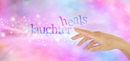 energising: Laughter is the Best Medicine  - Female hand pointing at a sparkly glittering LAUGHTER HEALS on a pink and blue bokeh background Stock Photo