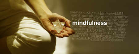 Mindfulness Meditation Word Cloud Banner - Female sitting in Lotus Position on left side with sunlight streaming in holding a Merkabah crystal meditating and a mindfulness word cloud on right side Stock Photo