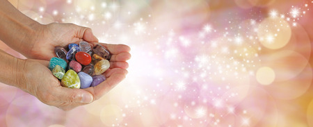 terminated: Crystal Therapist Sparkling Website Banner - female crystal therapist holding and offering a  selection of crystals on a wide sparkling orange background
