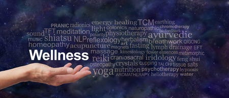 word: Your Wellness is in your hands  - Female hand outstretched with the word WELLNESS floating above, surrounded by a word cloud on a dark blue night sky background Stock Photo