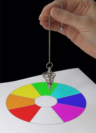 sectioned: Radionics practitioner with Color Dowsing chart - female hand holding a spiral dowsing pendulum over a color filled circular sectioned dowsing chart on a black background