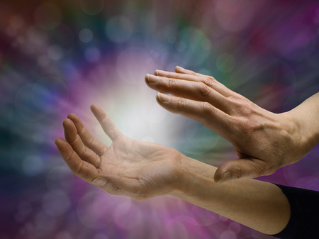 Sensing Paranormal activity - female hands sensing white energy  orb between hands on a dark multicolored bokeh background with copy space all around Stock Photo