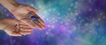 allergy questions: Choose a dowsing pendulum that resonates with you - Female dowsing practitioner holding four radionics pendants in an offering gesture on a wide blue green ethereal  background with copy space Stock Photo
