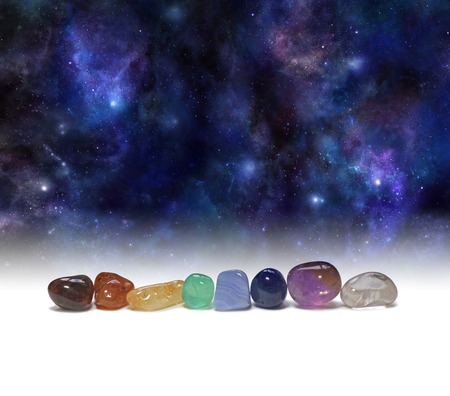 stones: Cosmic Chakra Healing Stones - a row of chakra colored tumbled healing crystals set against a background of the Universe providing copy space above Stock Photo