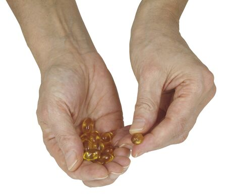 one female: Are you getting your daily Cod Liver Oil - female hand holding golden colored vegetable capsules offering one isolated on a white background
