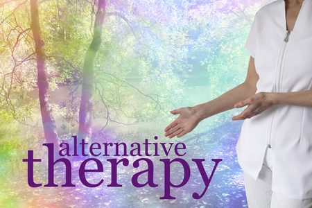 complementary therapy: Come and try our Alternative Therapies -  female holistic therapist gesturing to the words ALTERNATIVE THERAPY on a colorful rainbow tinted tree scenery background with copy space Stock Photo