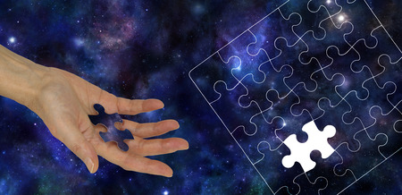 hand outline: The Missing Piece of the Universe - Female hand holding a piece of jigsaw imprinted with the Universe on a Blue Universe Deep Space background and a jigsaw puzzle outline on right side Stock Photo