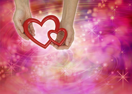 Two Love Hearts Valentine theme background - female hands holding an empty double heart shaped frame on a warm red pink swirling lines random background