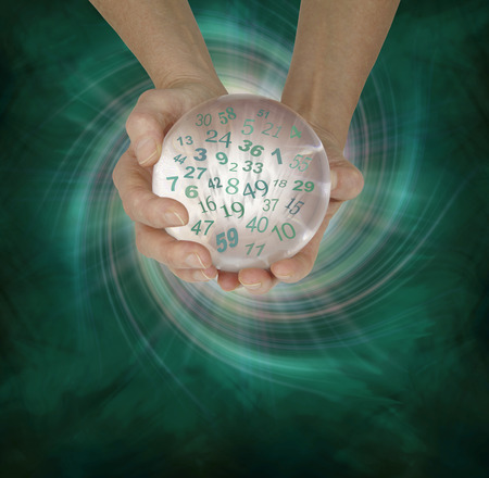pseudoscience: Lucky Lottery Numbers 1 to 59 - female hands cupped around a large crystal ball with random lottery numbers emerging  on a  green black spiraling energy field background with copy space below