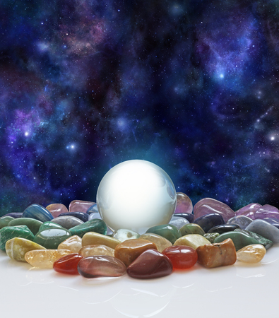 scrying: Crystal ball, healing crystals and the Universe - large clear crystal ball with a selection of chakra colored healing crystals with a background of the night sky deep space