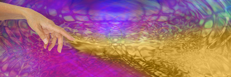 speculative: The Alchemist - female hand with index finger pointing and a stream of gold flowing out across the wide background of pink and purple psychedelic pattern Stock Photo