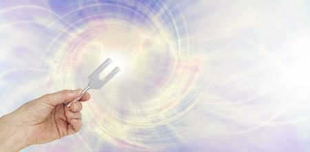 Si pudieras ver las ondas de sonido hacer por un ángel Tuning Fork - mano femenina que sostiene un túnel de ajuste de aluminio corto en una representación gráfica de las ondas de sonido angélico de fondo