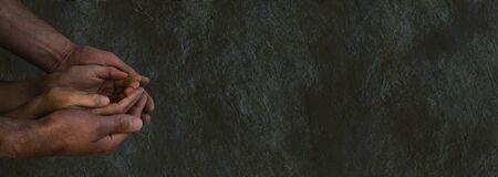 altruismo: Tiempos oscuros y desesperados - fondo oscuro amplia piedra en bruto grunge con las manos de un hombre que acunan manos de una mujer en forma de copa pidiendo gesto con la iluminación oscura y un montón de espacio de la copia