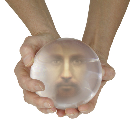 scrying: Crystal Ball Reading -  Female holding a large crystal scrying ball with a clear male face staring out with beautiful mesmerizing eyes Stock Photo