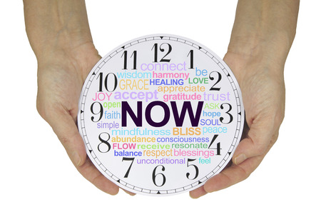 resonate: There is always only NOW - female hands holding a clock face with a NOW word cloud isolated on a white background Stock Photo