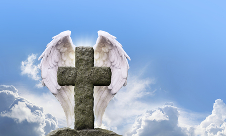 Angel Wings and Rustic Cross - highly detailed Angel Wings either side of a rustic stone cross with a bright sunny blue sky background and fluffy clouds behind with plenty of copy space Stock Photo