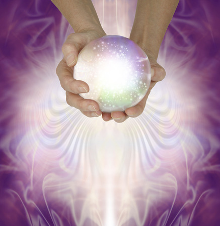 Let me read your fate and fortune in the crystal ball - Female fortune teller holding a large sparkling crystal ball in cupped hands against a magenta patterned background with copy space beneath Stok Fotoğraf