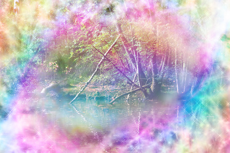 Ethereal Riverside Woodland Scene - rainbow colored riverside woodland path scene with streams of rainbow colored sparkling light making a circular frame around the center Stock Photo