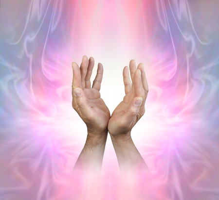 Male hands sensing Feminine Energy Field - male hands reaching up into a pink stream of light on a beautiful ethereal Angelic energy background with copy space