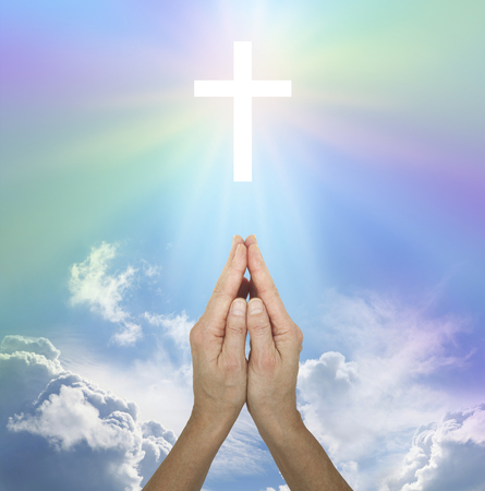sacred source: Thank You for my Bliss - female hands in prayer position pointing to a white glowing cross in the sky with a soft rainbow radiation and fluffy white clouds below Stock Photo