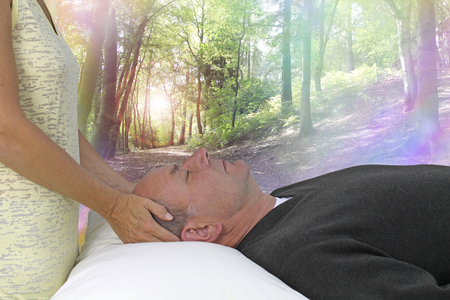 Dream State Spiritual healing session - female hands laid gentle either side of a male patient's head channeling healing energy with a beautiful woodland rainbow bokeh scene background photo