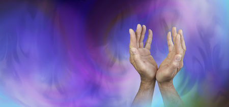 prana: Seeking Support from Higher Powers - Male hands reaching up with an ethereal gaseous swirling blue and magenta energy field behind and copy space on left side Stock Photo
