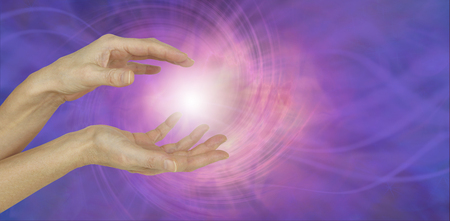 healing chi spiritual: White Orb Energy Between Hands - a pair of female hands with a white energy orb between on an ethereal pink and purple vortexing energy field background