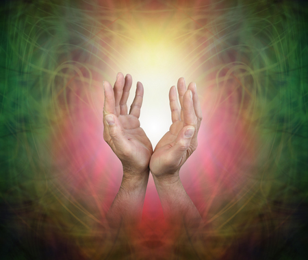 Male hands sensing Pranic Energy Field - male hands reaching up into a golden orb light on a beautiful ethereal green and red  vignette pattern background with copy space Stock Photo