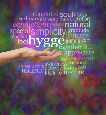 contentedness: Everybodys talking about HYGGE - female hand outstretched with the hip Danish word HYGGE floating above surrounded by a relevant word cloud on a vibrant modern painterly background
