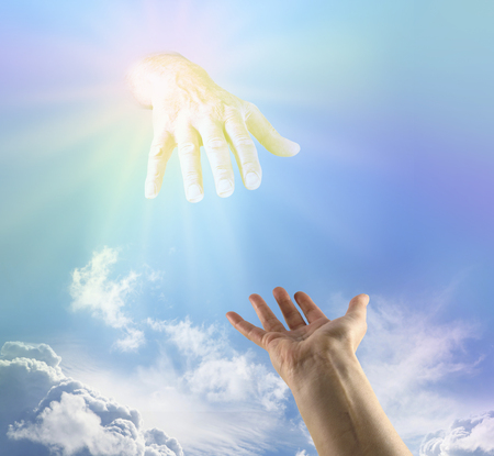 Asking for a Heavenly Helping Hand - female hand outstretched palm up reaching towards large golden flowing hand emerging from subtle rainbow colored light in the blue sky above depicting God Stock Photo