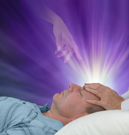 Spiritual help during a healing session - female hands laid on a male patients forehead channeling energy together with a higher power manifesting healing light on a dark purple background Stock Photo