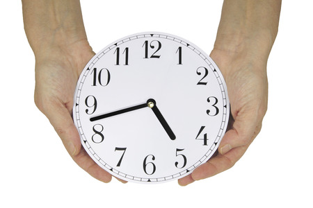 the daily grind: Nearly time to go home - female hands holding a clock face showing seventeen minutes to five, which is almost home time for many workers, isolated on a white background Stock Photo