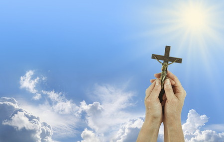 Praise to Our Lord - Female hands gently holding a Crucifix of Jesus Christ up towards a shining sun in a blue sky background with copy space on the left Stock Photo