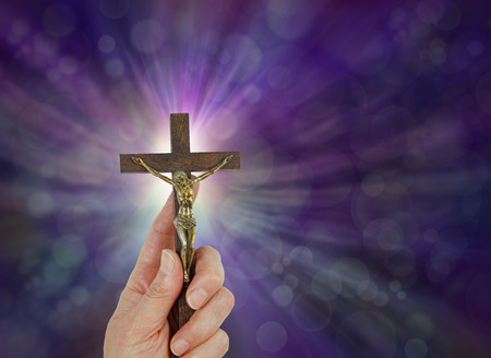 The Greatest Love - Female hand holding a Crucifix of Jesus Christ up against a purple bokeh background with a radiating light burst behind the cross intersection and copy space on the right Stock Photo